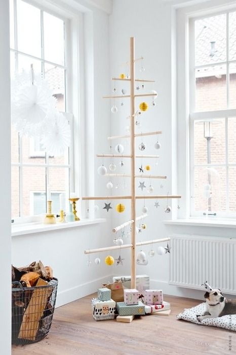 a white metal Christmas tree with ornaments and stars for a Scandinavian space