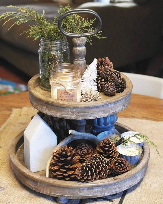 a wooden stand with pinecones, tinsel trees, candles and evergreens for a rustic feel