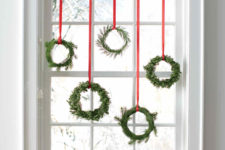 DIY small evergreen Christmas wreaths on red ribbons