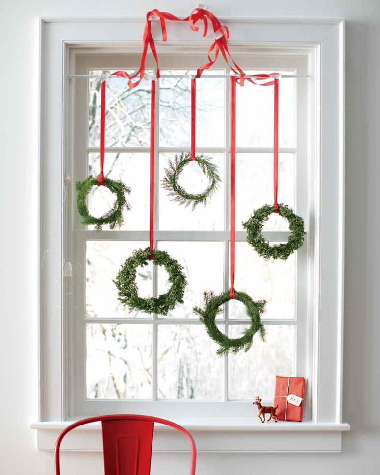 DIY small evergreen Christmas wreaths on red ribbons (via www.marthastewart.com)