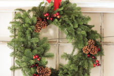 DIY evergreen Christmas wreath with berries and pinecones