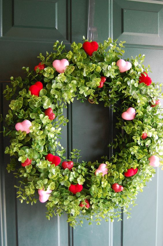 a grapevine wreath with boxwood picks and red and pink hearts here and there