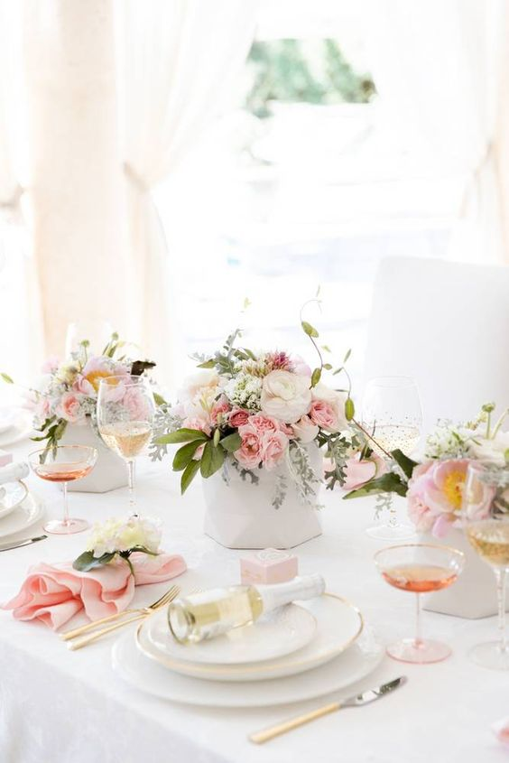 a chic tablescape with cream and pink blooms, with blush napkins and gilded touches