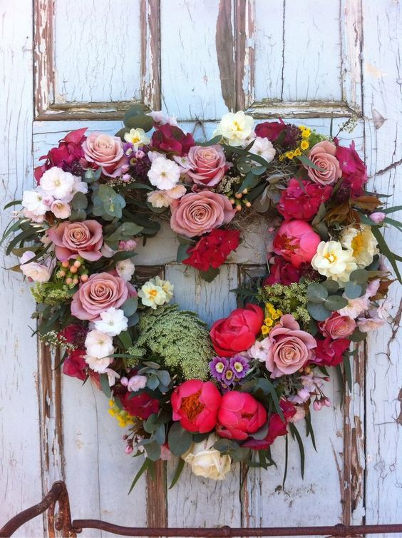 a faux floral and greenery wreath shaped as a heart
