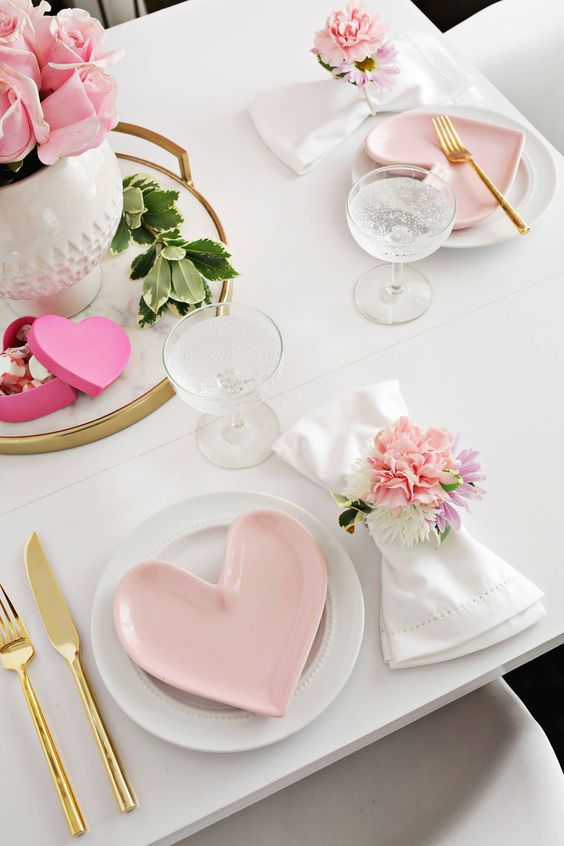 a cute and girlish table setting with pink heart-shaped plates and some more pink touches