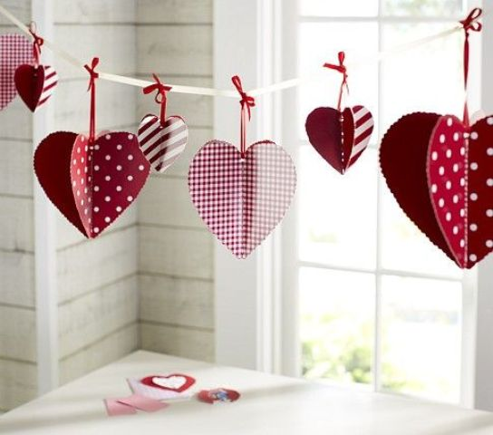 3D colorful paper hearts attached to a thread using ribbon bows