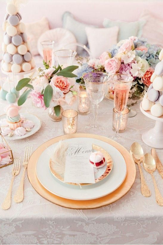 a cute galentine table setting with a macaron tower, plates and gilded touches