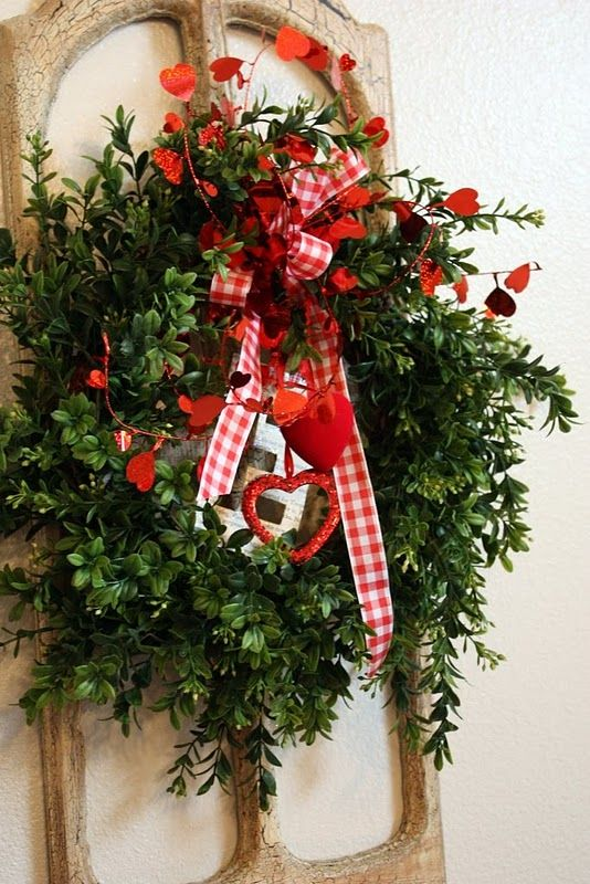 a faux greenery wreath with red paper hearts, checked ribbon bows and some hanging hearts