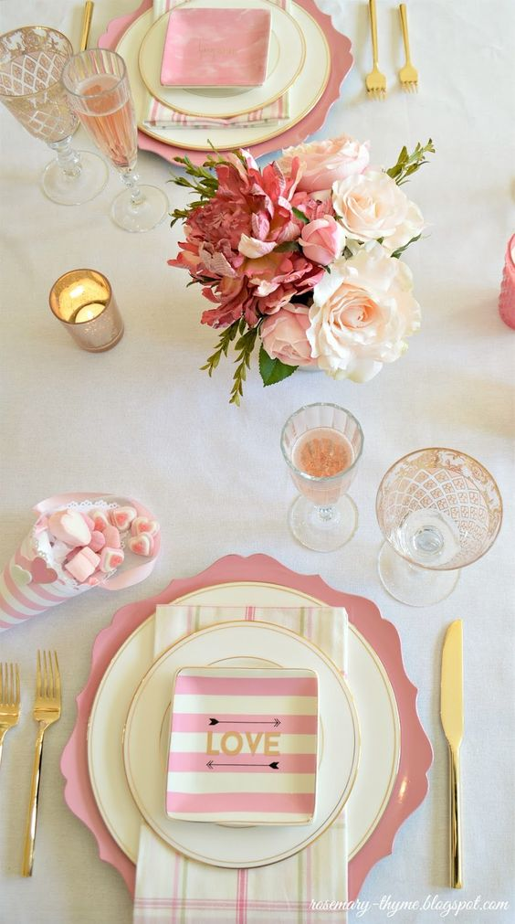 a cute tablescape in pink, cream and gold with pink blooms, striped plates and napkins and candies