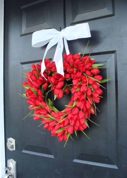 a red tulip wreath shaped as a heart with a large ribbon bow, it can be natural or not