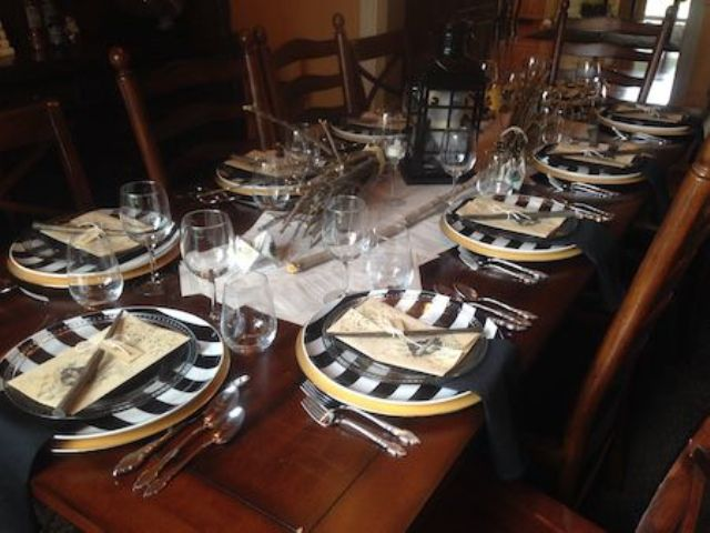 a cool tablescape with striped chargers, sheer plates, a lantern and wands for each place setting