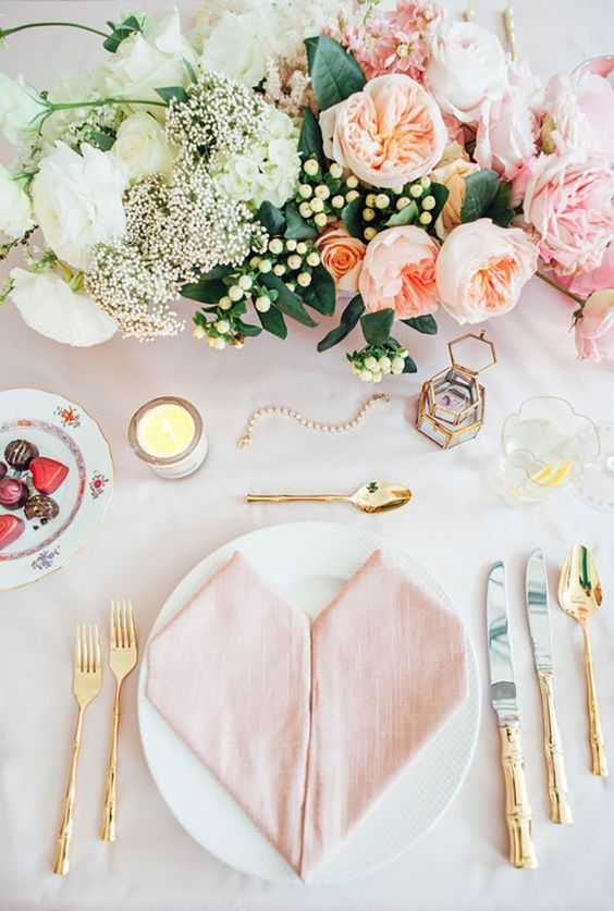 a stylish setting with pink and cream blooms, a pink heart-folded napkin and gold touches