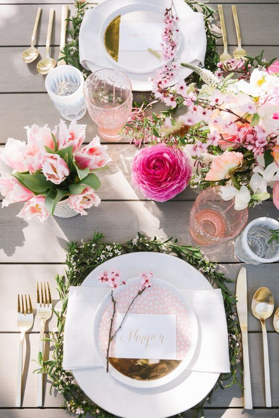 a cute setting with greenery and pink spring blooms, giklded touches and colored glasses