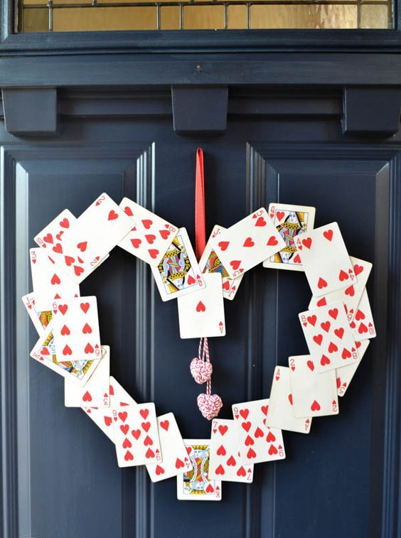 a heart-shaped play card wreath with a couple of yarn hearts hanging