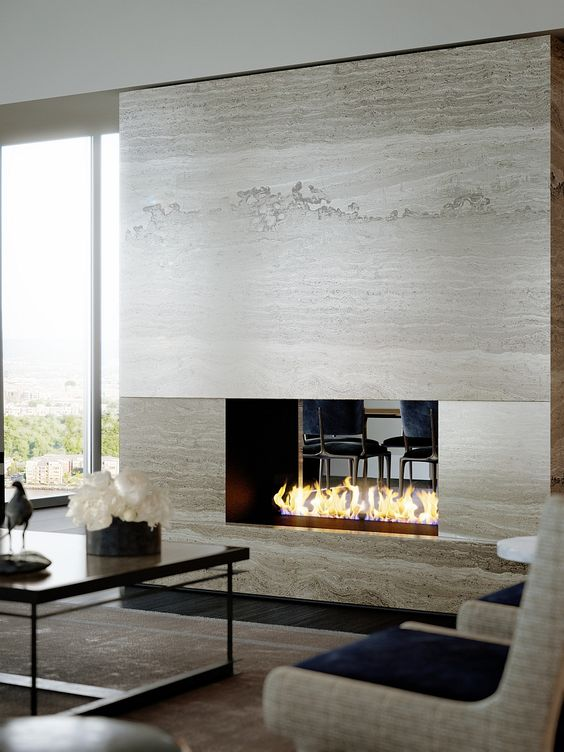 a luxurious double-sided fireplace becomes a focal point both in the living room and dining room