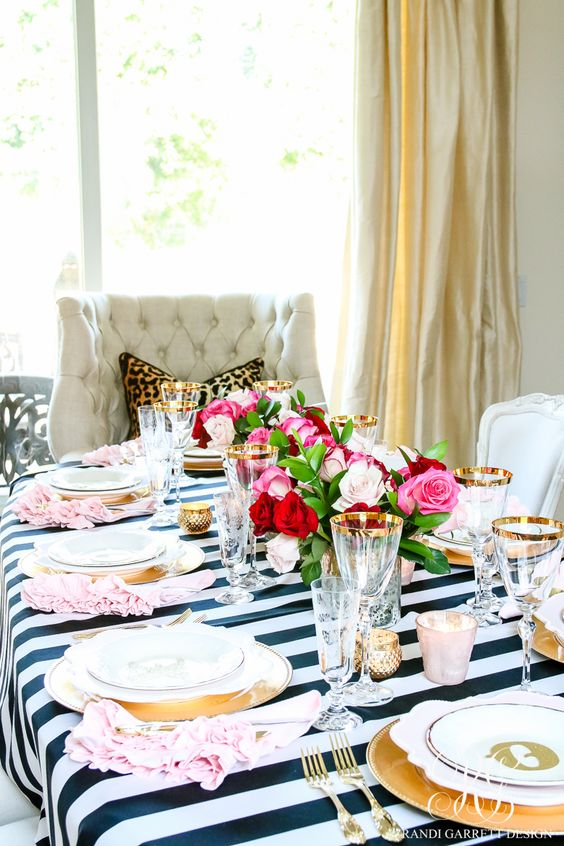 a colorful tablescape with a black and white tablecloth, gold touches and red and pink blooms