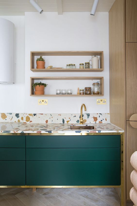a bold emerald cabinets with brass framing and colorful terrazzo countertops