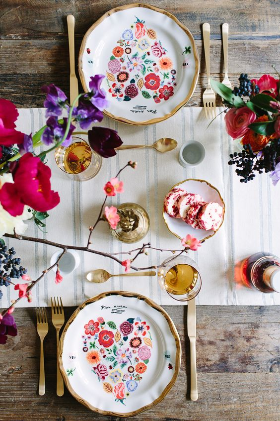 a fun galentine setting with floral print heart plates, a striped runner and bold blooms