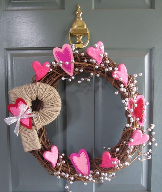 a grapevine wreath with pearls, bold pink hearts and a twine wrapped monogram