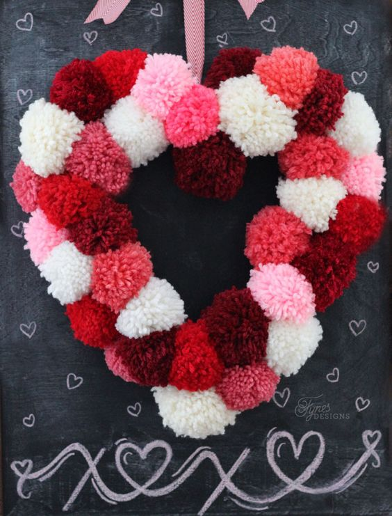 a colorful pompom heart in shades of red and pink can be easily DIYed