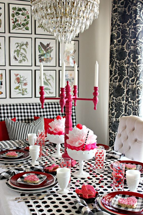 a modern black, white and pink tablescape with candles, heart shaped pieces and lots of patterns