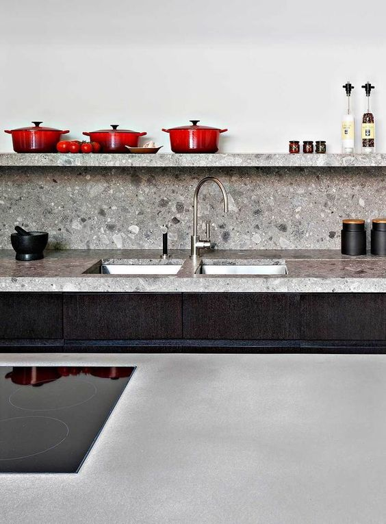 grey terrazzo countertops and backsplash match the dark stained cabinets