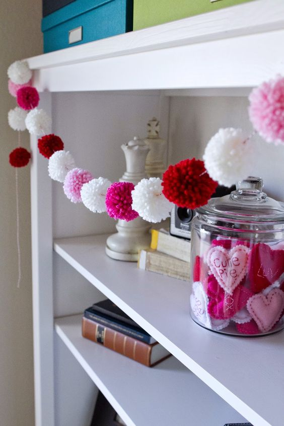 a cute white, pink and red pompom garland is a nice and fast to realize idea
