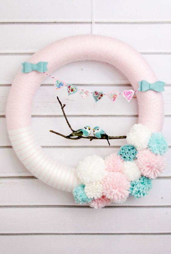 a pink wreath with a heart banner, bows, pompoms and a couple of lovebirds