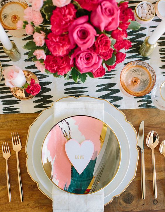 a printed table runner, hot pink blooms, gold touches and creative chargers