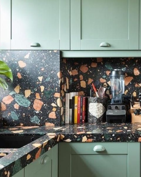 light green cabinets with dark terrazzo countertops and a backsplash that match