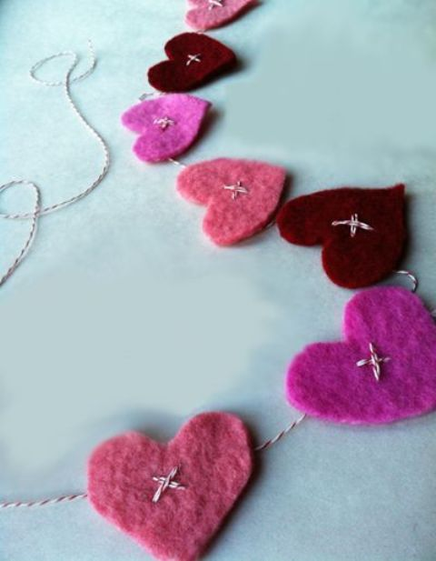 a Valentine's Day garland of colorful felt hearts attached to the thread with embroidery