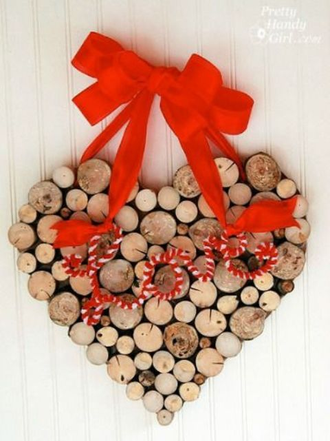 a pretty wood slice heart shaped wreath with a yarn word and a bold red bow