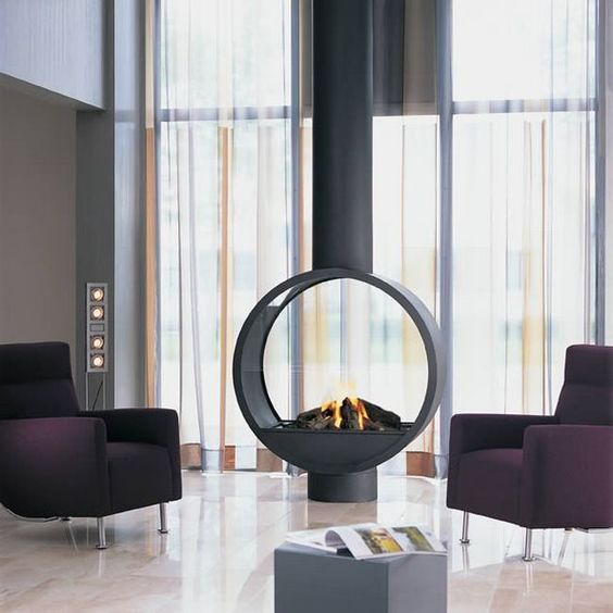 a suspended round fireplace is the center of attraction in this modern living room