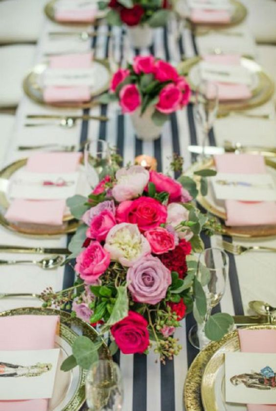 an elegant galentine tablescape with a striped runner, gold rim plates, pink napkins and bold pink florals
