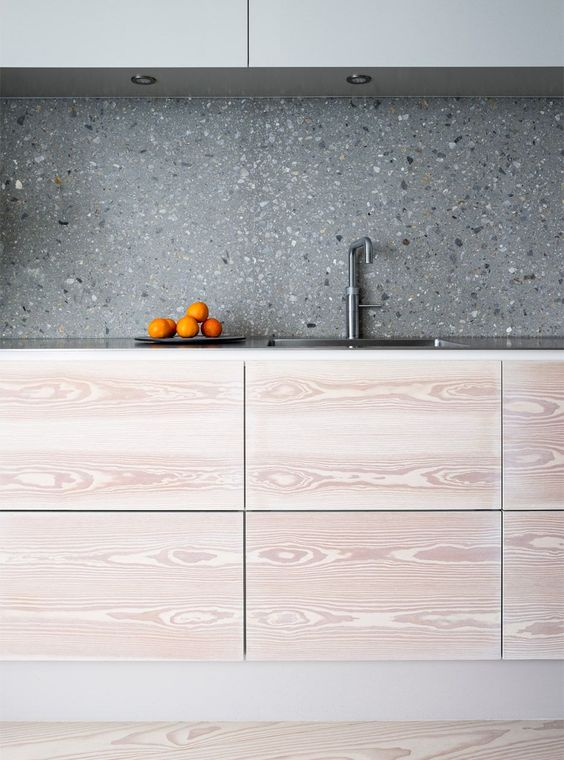 light-colored plywood cabinets and grey terrazzo backsplash that matches the uppers
