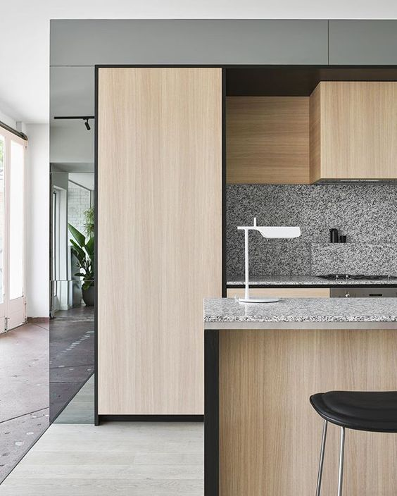 light-colored wooden cabinets with grey confetti terrazzo countertops and a backsplash