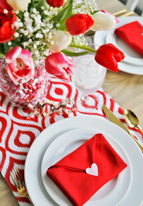 red envelope-shaped napkins, a red and white table runner, a bold centerpiece with blooms and candies in the vase