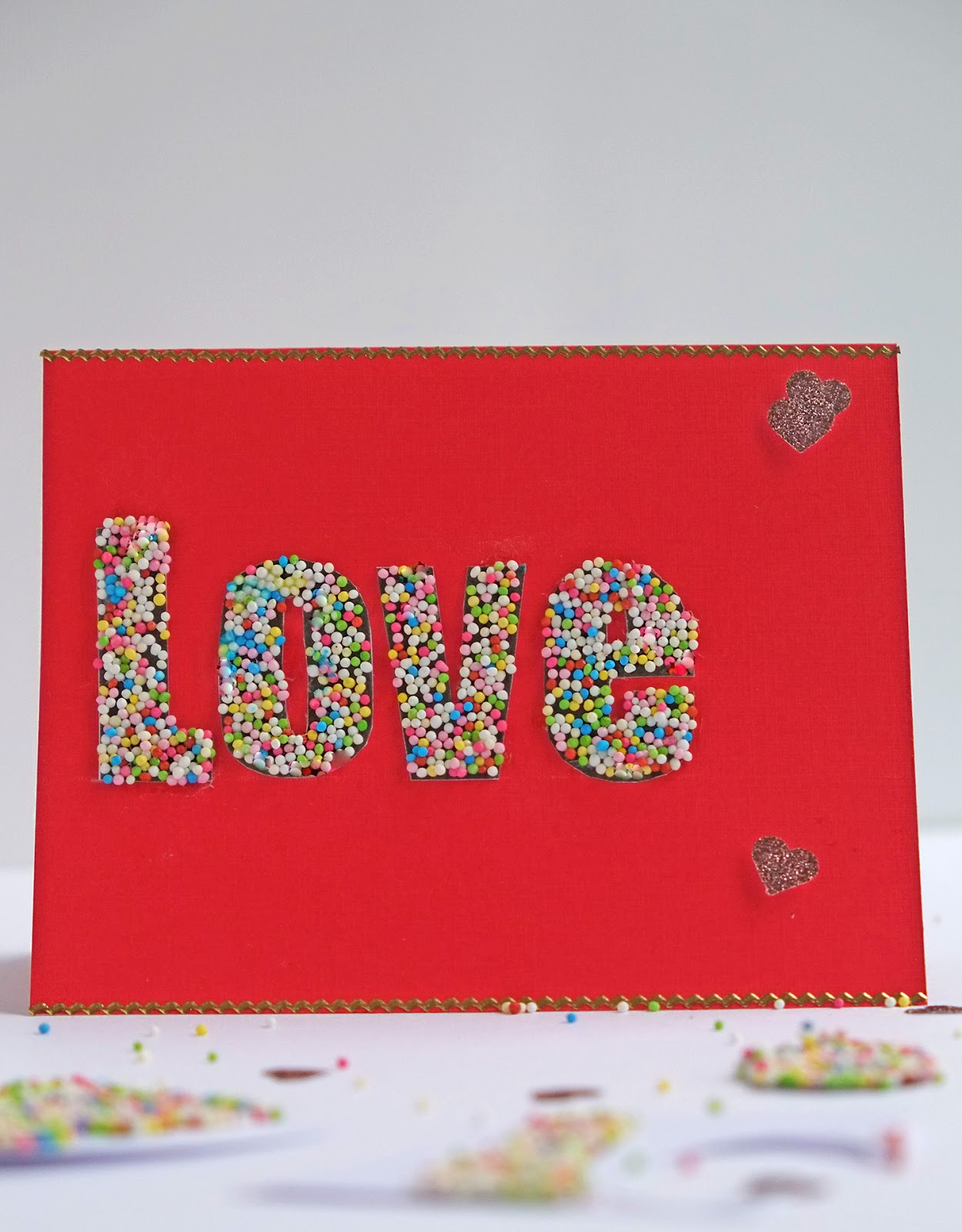 DIY red cardboard card with sprinkle covered LOVE