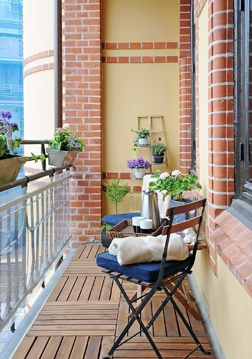 a small balcony with a couple of folding chairs with cushiones, a foldable table and plants with bright flowers