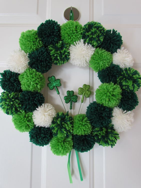 a white and green pompom wreath with glitter shamrocks for decor