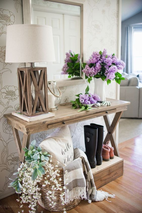 a console styled with fresh blooms and a basket with faux blooms and greenery for a farmhouse space