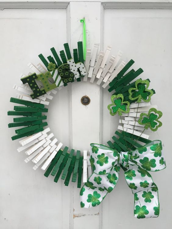 a green and white wreath of clothespins, with painted letters, glitter shamrocks and a printed bow