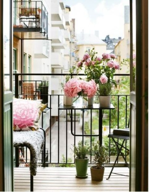 a tiny balcony with a small bench, a foldable chair and table plus pink blooms in pots