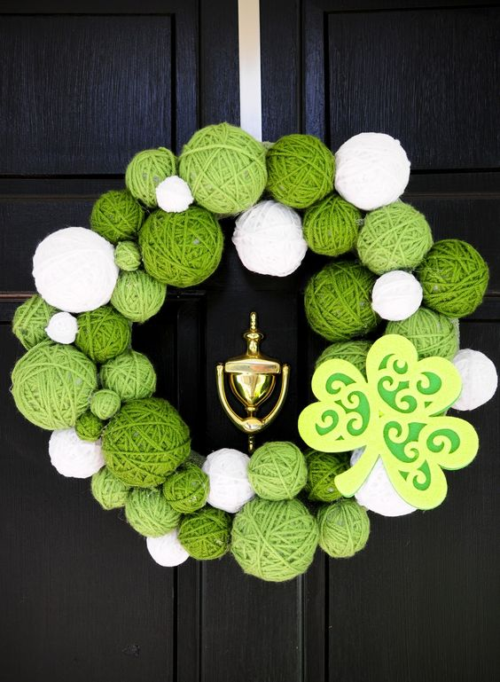 a wreath of white and green yarn balls and a cardboard shamrock looks bold and creative