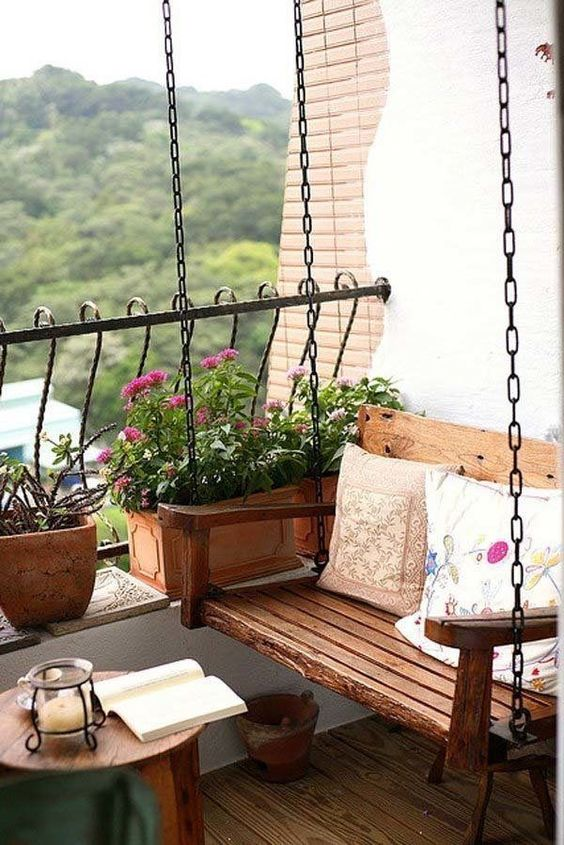 a swing bench, a wooden table and wooden planters that match the furniture look