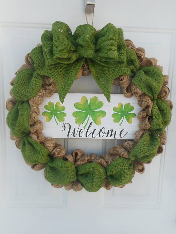 a usual and green burlap wreath with a large bow and a wooden plaque with shamrocks