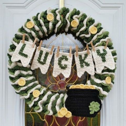 a fully crocheted wreath with a pot of gold, a bunting and gold coins here and there