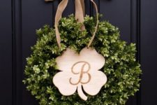 09 a cool boxwood wreath with a wooden shamrock-shaped plaque and a burlap bow