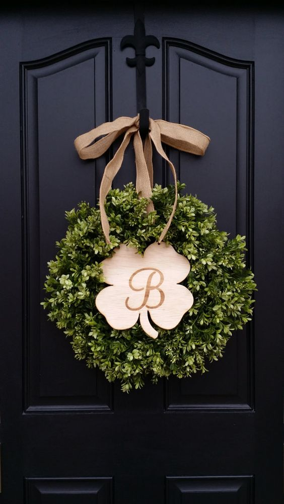 a cool boxwood wreath with a wooden shamrock-shaped plaque and a burlap bow