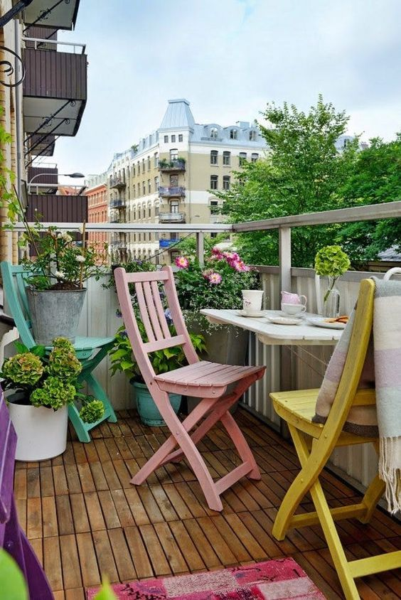 pastel-colored folding chairs plus rugs and fresh greenery for a spring-ready balcony